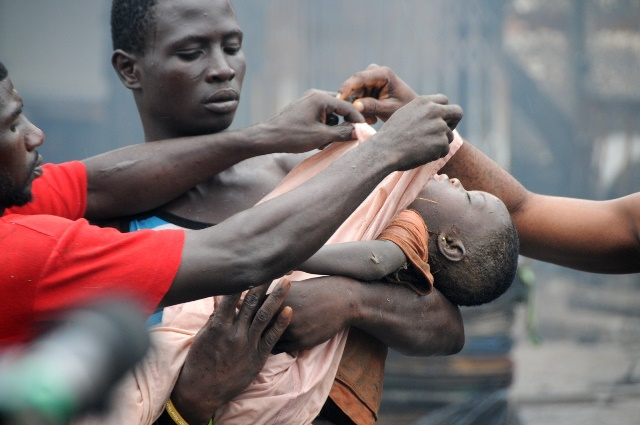 A Rescue worker carries the body of a three-year-old victim that was killed after a fuel station explosion in Accra, capital of Ghana, June 4, 2015.Over 96 people were killed in a fuel station explosion in Accra, official of the fire service confirmed. Prince Billy Anaglatey, the Deputy Public Relations Officer of the Ghana National Fire Service (GNFS) said the agency retrieved the bodies from the debris of the Goil filling station located at the circle on Wednesday night. A large number of the victims were seeking refuge at the fuel station after a heavy downpour when the explosion occurred. Many parts of Accra were completely submerged after several hours of torrential rains on Wednesday night leaving many roads impassable and residents homeless. (Xinhua/Lin Xiaowei)