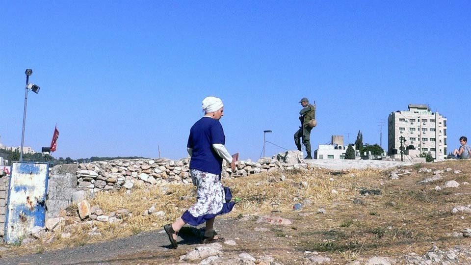 A settler woman walks past an Israeli soldier standing guard in East Jerusalem. Photo: IRIN/Andreas Hackl (file photo)