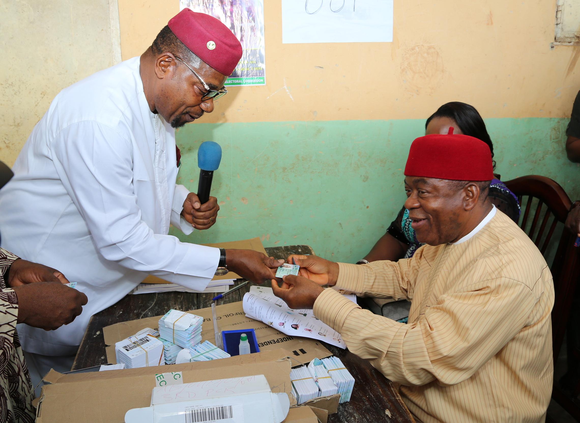 Gov. Theodore Orji of Abia state receiving his permanent voter?s card from Amb. Lawrence Nwuruku, National Commissioner INEC at Ugba ward 1 in Umuahia.