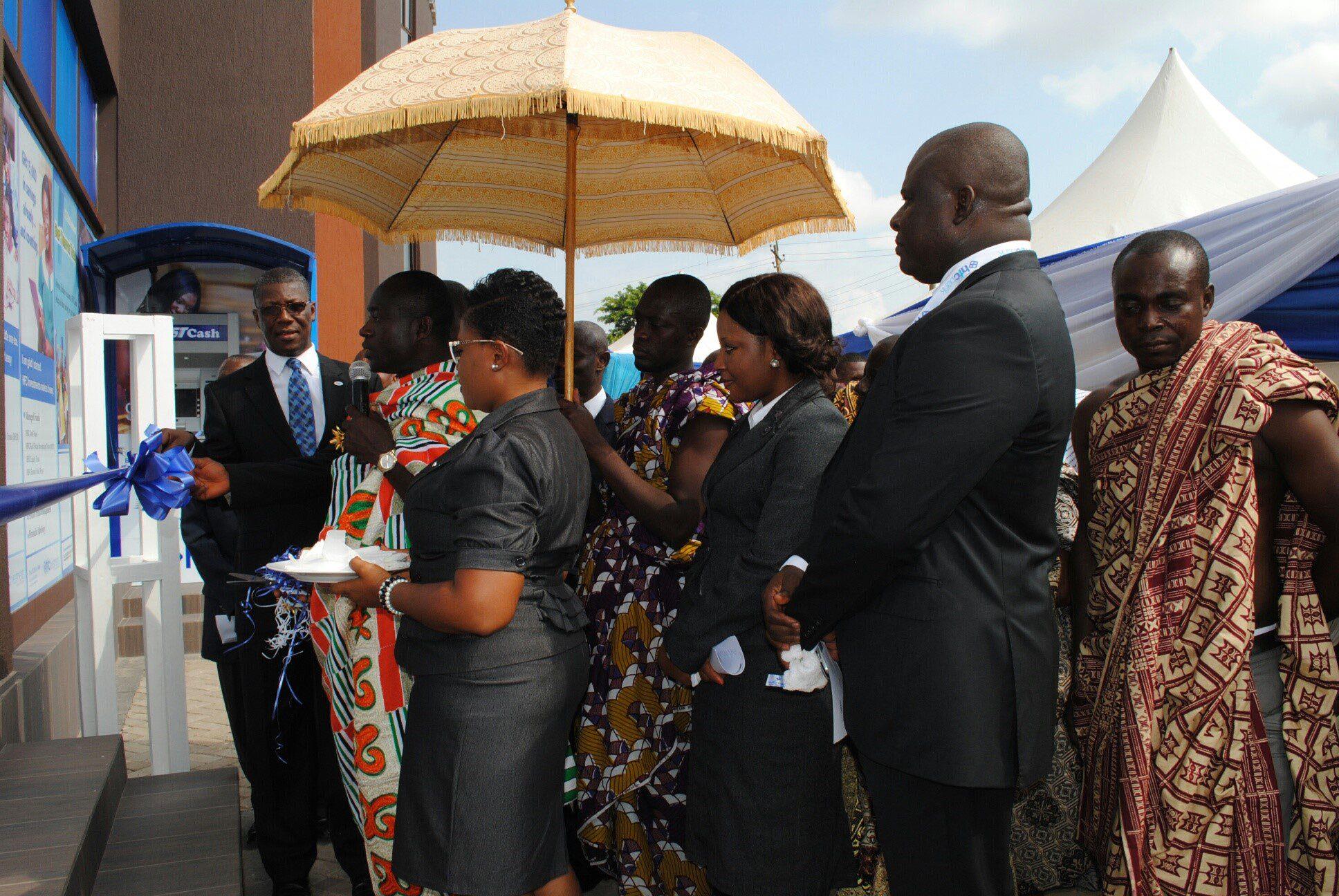Nana Adu Mensah Asare, Amakomhene, helps Mr Asare Akuffo, MD of??HFC Bank (facing camera) to cut the tape for the inauguration ?