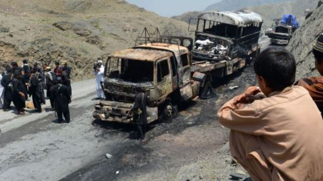 Pakistani security personnel gather beside torched NATO supply trucks after an attack by militants in the northwestern Khyber region. (File photo)