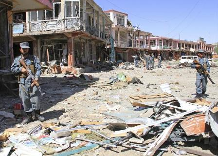 Afghan police stand guard among damaged buildings after a suicide attack in Ghazni province, Sept. 4, 2014. Taliban insurgents detonated truck bombs and fired rocket-propelled grenades outside the office of Afghanistan's spy agency and a police compound in the central town of Ghazni on Thursday, the provincial governor said. Reuters/Mustafa Andaleb