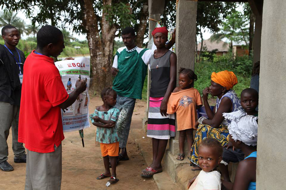 A team of volunteers in Gbaneh Bana Village, Port Loko District, Sierra Leone, discussing Ebola prevention with a family. Photo: WHO/S. Gborie