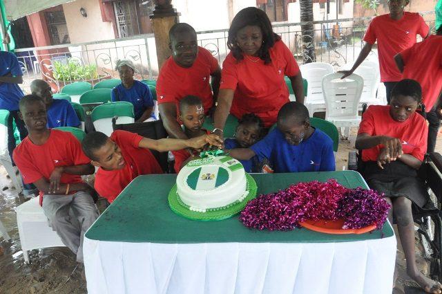 Head, Corporate Communications, Dana Air, Mr. Samuel Ogbogoro (standing Right) and Matron, Sai Orphanage, Mrs. Darshaua Deko Okitikpi with the special children cutting the cake to mark Nigeria?s 54th Independence Anniversary.