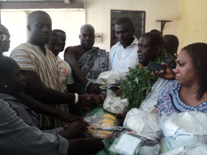 Nii Ayaafio (in smock) in a handshake after receiving the items from Mr Akwetey