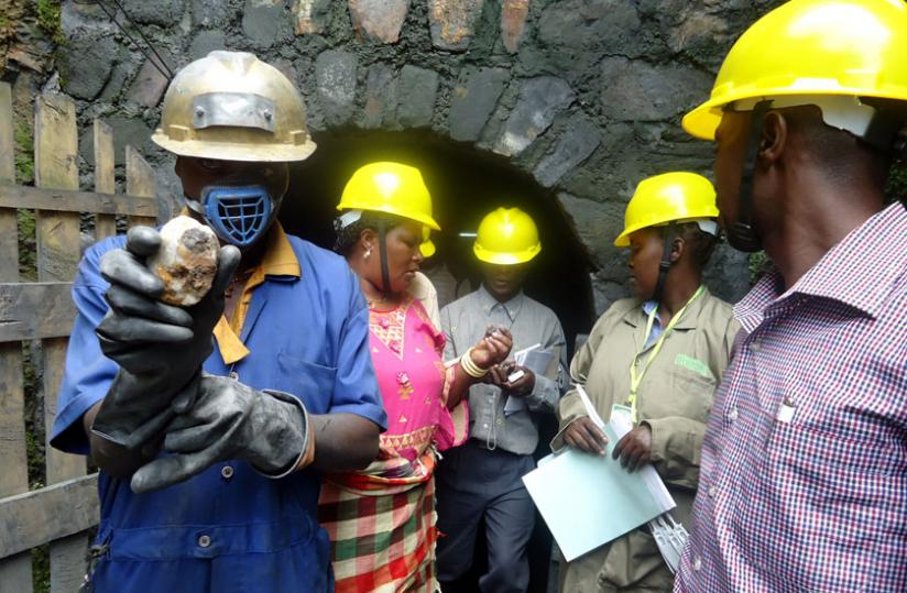 Members of the delegation with workers at Gifurwe Wolfram Mining Company look at the minerals as they get out of the tunnel on Tuesday. (Emmanuel Ntirenganya)