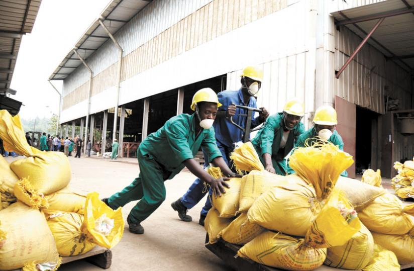 Workers at Phoenix Metals Ltd push bags of minerals after weighing them at the plant yesterday. (John Mbanda)