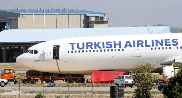 Photo taken on March 6, 2015 shows the crash-landed Turkish Airlines Flight TK726 during the process of pushing it back to the runway at Tribhuwan International Airport in Kathmandu, Nepal. The Tribhuwan International Airport, Nepal's only international airport, has remained shut for the past three days following Turkish Airlines Flight TK726 skidding off the runway after landing since Wednesday morning. All international flights have been suspended and about 40,000 passengers remain stranded. (Xinhua/Sunil Sharma) (dzl)