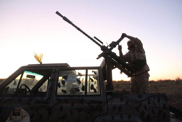 A Libya Dawn fighter reloads a machine gun near Libya's capital city of Tripoli, on March 11, 2015. Clashes erupted on Wednesday between Libya Dawn militants and pro-government forces in the Ajaylat area some 80 kilometers west of Tripoli. (Xinhua/Hamza Turkia)