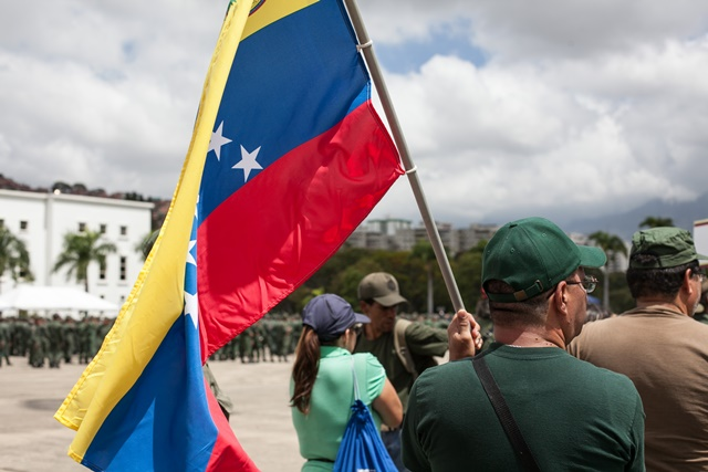 A citizen holds a Venezuelan national flag during the military exercises convened by Venezuelan President Nicolas Maduro, in Caracas, Venezuela, on March 14, 2015. Venezuelan Defense Minister Vladimir Padrino Lopez inaugurated the ten-day military exercises on Saturday, which he said was launched due to the urgent need to defend the integrity of the nation. (Xinhua/Boris Vergara) (jg)