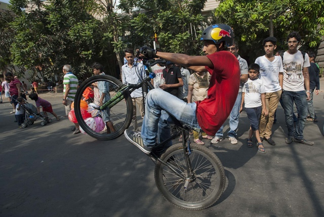 """An Indian boy practises cycling at one of the main streets as the street was closed for vehicles and open for fun in Kolkata, capital of eastern Indian state West Bengal, March 15, 2015. As part of a new initiative named """"Happy Street"""", for four consecutive Sundays, vehicles will be barred from entering this area for three hours in the morning. (Xinhua/Tumpa Mondal)"""
