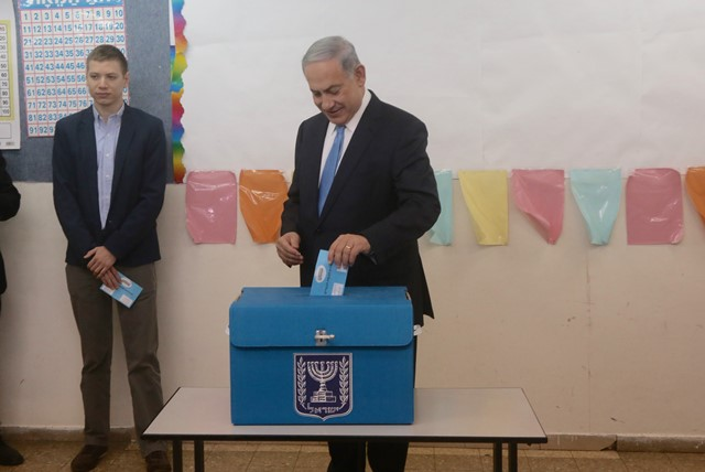 Israeli Prime Minister Benjamin Netanyahu (R) casts his ballot at a polling station during the parliamentary election in Jerusalem, on March 17, 2015. Israel held parliamentary election on Tuesday. (Xinhua/JINI/POOL/Marc Israel Sallem)
