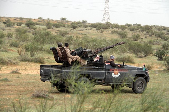Some Libya Dawn fighters prepare to enter the combat zone on their armed vehicles near Bir al-Ghanam, Libya, on March 21, 2015. Clashes continued between Libya Dawn fighters and pro-government forces on Saturday near Bir al-Ghanam, some 90 kilometers southwest of the capital Tripoli. (Xinhua/Hamza Turkia)