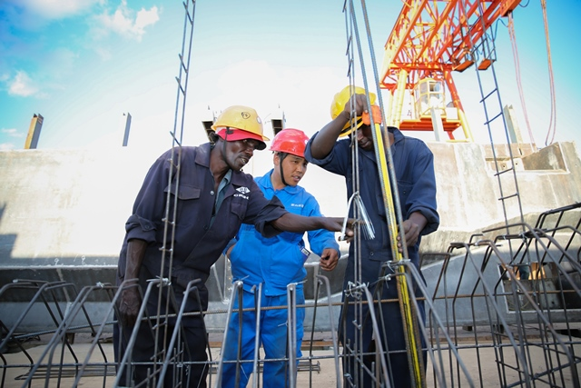Wang Xinjiang (C), a Chinese engineer, works with Kenyan workers at the T-beam factory on the section six of Kenya's Standard Gauge Railway project, near Makueni, Kenya, on March 16, 2015. The project, expected to cost 3.8 billion U.S. dollars, involves the construction of about 480 kilometer railway line from the port city Mombasa to the capital city Nairobi. China Roads and Bridges Corporation (CRBC) is undertaking the project. (Xinhua/Pan Siwei)
