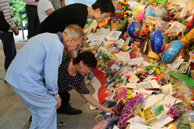 People mourn over the death of Lee Kuan Yew, former prime minister of Singapore, at the central hospital of Singapore, March 23, 2015. Lee Kuan Yew died at 3:18 am on Monday at the age of 91, according to a statement released by the Prime Minister's Office (PMO) on Monday. (Xinhua/Bao Xuelin)