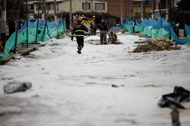 Firefighters work on a street after heavy rains in the city of Bogota, Colombia, on March 23, 2015. According to local press, several sectors of the Colombian capital city were affected by strong rain accompanied by hail on March 22, causing damage to hundreds of homes and generating floods. (Xinhua/Jhon Paz) (jp)