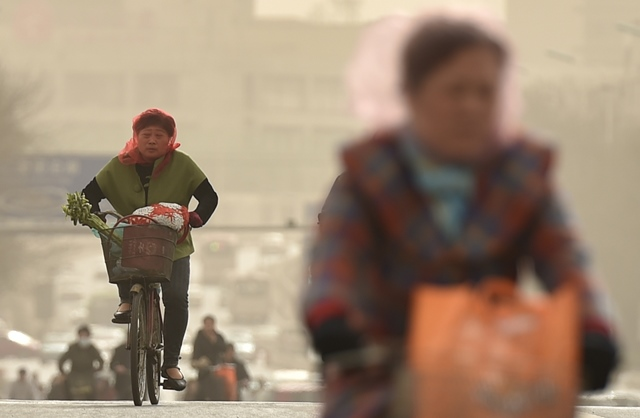 People ride in dusty wind with a veil on face on a road in Tianjin, north China, March 28, 2015. Part of Tianjin received dusty weather on Saturday. (Xinhua/Yue Yuewei) (zwx)