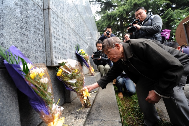 Survivor of Nanjing Massacre Chang Zhiqiang lays flowers in front of a wall inscribed the name list of victims at the Memorial Hall of the Victims in Nanjing Massacre by Japanese Invaders on the Qingming Festival in Nanjing, capital of east China's Jiangsu Province, April 5, 2015. Japanese troops captured Nanjing, then China's capital, on Dec. 13 of 1937 and started a 40-odd-day slaughter. More than 300,000 Chinese soldiers who had laid down their arms and civilians were murdered, and over 20,000 women were raped. (Xinhua/Han Yuqing) (lfj)