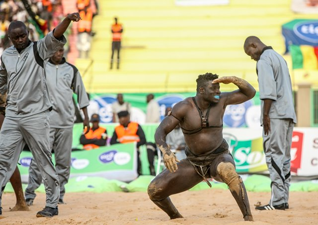 "A wrestler celebrates his victory in the Senegalese traditional wrestling match ""Le Choc"" at Demba Diop Stadium, Dakar, capital of Senegal, April 5, 2015. Thousands of audience have watched the biggest match here on Sunday at the beginning of the wrestling season with the most famous wrestlers Balla Gaye 2 and Eumeu Sene competing. Eumeu Sene won the match at last. (Xinhua/Li Jing)"