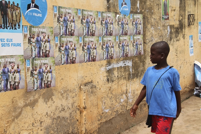 A boy passes by election campaign posters for Faure Gnassingbe, Togolese President in Lome, capital of Togo, April 13, 2015. Togo?s presidential elections will be held on 25 April 2015. (Xinhua/Zhang Gaiping)