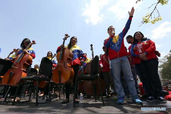People take part in an event, headed by Venezuela's Vice President Jorge Arreaza (2nd R, front), to collect signatures for a petition against the executive order of U.S. President Barack Obama which declares Venezuela as a threat to the national security of the U.S., in Caracas, Venezuela, on March 31, 2015. (Xinhua/Fausto Torrealba/AVN)