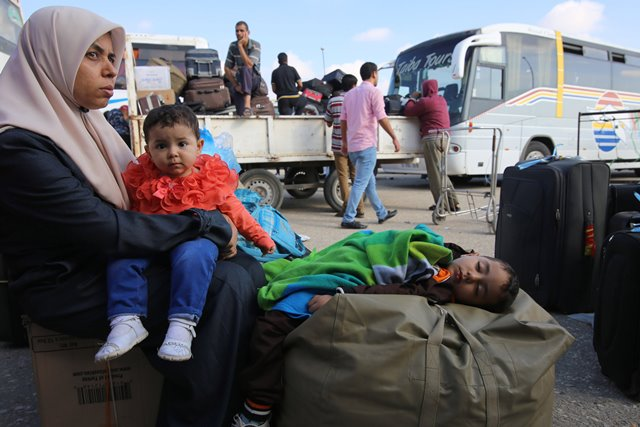 A Palestinian woman holds her boy as she waits for a travel permit to cross into Egypt, at the Rafah border crossing between Egypt and the southern Gaza Strip, June 13, 2015. Egyptian authorities opened the Rafah border crossing on Saturday for three days, in both directions to allow entry and exit of Gazan patients and students, for the first time since March 11, Palestinian officials said. (Xinhua/Khaled Omar) (zjy)