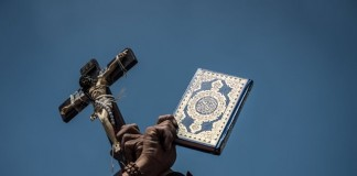 An Egyptian protestor holds the Quran and a cross as mourning over Egypt's Prosecutor General Hisham Barakat in eastern Cairo, capital of Egypt, on June 30, 2015. Barakat died Monday in a hospital in Cairo from injuries sustained in a car bomb attack earlier in the day. (Xinhua/Pan Chaoyue)
