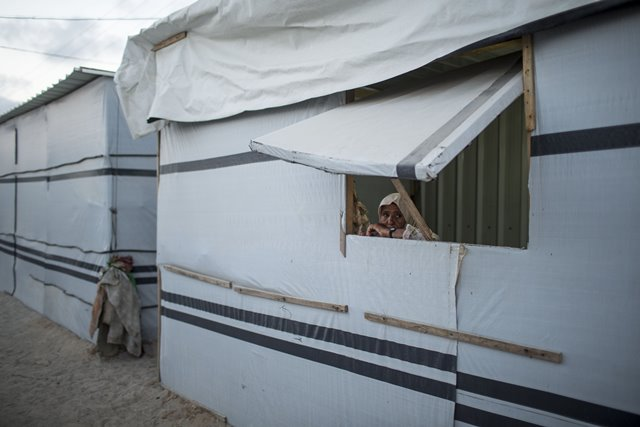 """A Palestinian woman looks out from the window of her temporary house """"caravan"""" in the southern Gaza Strip city of Khan Younis on July 7, 2015. The 50-day war between Israel and Gaza Hamas-led militant groups ended after Egypt brokered a truce between the two sides. However, people in the coastal enclave still live amid poverty, unemployment and the ongoing endless Israeli blockade. (Xinhua/Wissam Nassar)"""