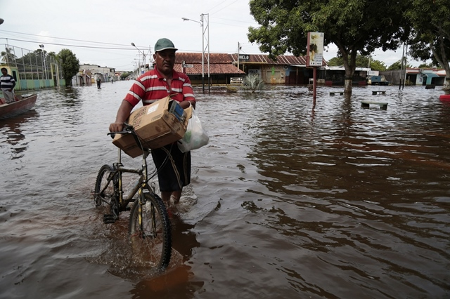 A person walks with his bicycle in a flooded street in the town of Guasdualito, Apure state, Venezuela, on July 7, 2015. According to local press, more than 9,000 families were affected by the floods caused by the overflowing of the rivers Arauca and Sarare. (Xinhua/Str) (jp)