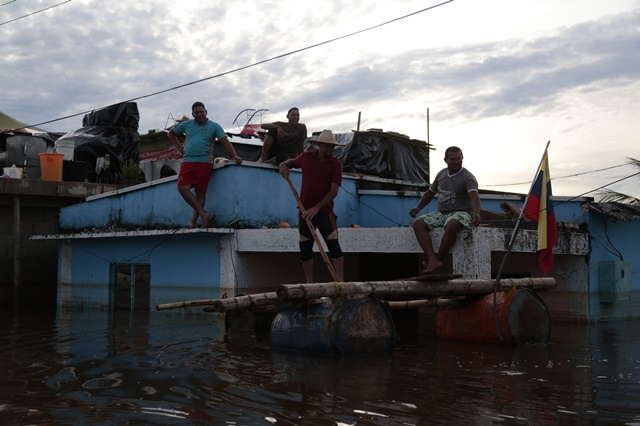 People move on board a improvised boat in a flooded street in the town of Guasdualito, Apure state, Venezuela, on July 7, 2015. According to local press, more than 9,000 families were affected by the floods caused by the overflowing of the rivers Arauca and Sarare. (Xinhua/Str) (jp)
