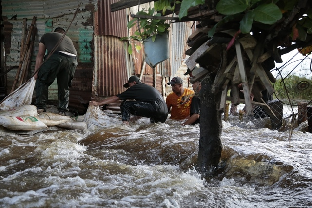 People try to rescue their belongings in a flood in the town of Guasdualito, Apure state, Venezuela, on July 7, 2015. According to local press, more than 9,000 families were affected by the floods caused by the overflowing of the rivers Arauca and Sarare. (Xinhua/Str) (jp)