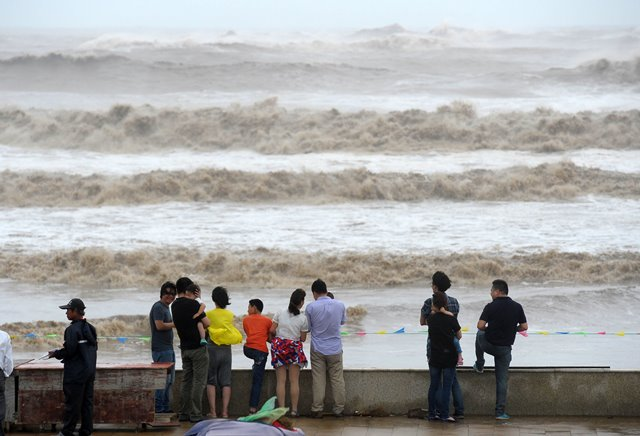 People watch huge waves at a dock in Zhoushan City of east China's Zhejiang Province, July 10, 2015. Typhoon Chan-Hom is expected to land somewhere between Sanmen and Zhoushan in east China's Zhejiang Province on Saturday afternoon, the National Meteorological Center (NMC) forecast.  (Xinhua/Wu Linhong) (zwx)