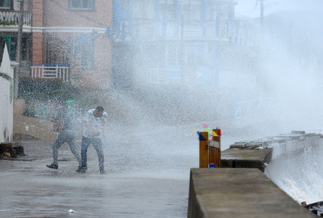 People are hit by splashing water from a bank at a scenic spot in Zhoushan City of east China's Zhejiang Province, July 10, 2015 . Typhoon Chan-Hom is expected to land somewhere between Sanmen and Zhoushan in east China's Zhejiang Province on Saturday afternoon, the National Meteorological Center (NMC) forecast.  (Xinhua/Wu Linhong) (zwx)