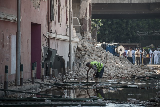 A Security man checks the explosion site in front of Italian consulate in downtown Cairo, Egypt, July 11, 2015. A powerful explosion occurred in front of Italian consulate in downtown Cairo Saturday, killing one person and injuring four, state-run news agency MENA reported.  (Xinhua/Pan Chaoyue) (cl)