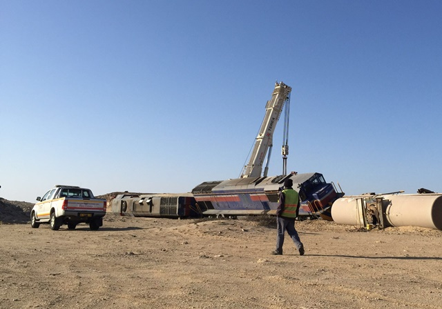 A worker walk past a derailed locomotive near the port of Walvis Bay, Namibia, July 14, 2015. National Railway carrier of Namibia, Transnamib's train derailed on Monday evening with a load of 20 Sulphuric acid tankers, no injuries or leakage were recorded. (Xinhua/Cui Hailong)