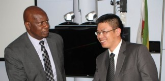 Zimbabwean Finance Minister Patrick Chinamasa (L) congratulates Huang Changbiao, General Manager for Eastern and Southern Africa of China State Construction Engineering Corporation (CSCEC) in Harare, Zimbabwe, July 23, 2015. The CSCEC was awarded the contract to build the phrase one of the coal-fired Lusulu power plant with generation capacity of 600 MW at a cost of 1.1 billion U.S. dollars. (Xinhua)