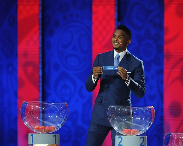"""Cameroon's soccer player Samuel Eto'o holds up the slip showing """"Cameroon"""" during the preliminary draw for the 2018 FIFA World Cup at Konstantin Palace in St. Petersburg, Russia July 25, 2015. (Xinhua/Dai Tianfang)"""