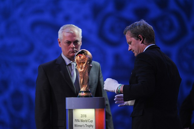 An official (R) puts the World Cup Trophy on display during the preliminary draw for the 2018 FIFA World Cup at Konstantin Palace in St. Petersburg, Russia July 25, 2015. (Xinhua/Dai Tianfang)
