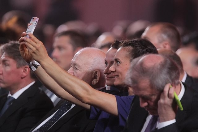 Russia's famous pole vault athlete Yelena Isinbayeva (2nd R) takes photos during the preliminary draw for the 2018 FIFA World Cup at Konstantin Palace in St. Petersburg, Russia July 25, 2015. (Xinhua/Lu Jinbo)