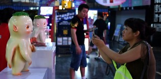 """A spectator takes photos for Huba, a monster in the film """"Monster Hunt"""", at a cinema in Shenyang, capital of northeast China's Liaoning Province, July 26, 2015. Live-action animation """"Monster Hunt"""" has become the most successful Chinese film of all time, the country's entertainment watchdog said Sunday. According to the State Administration of Press, Publication, Radio, Film and Television, Monster Hunt had raked in more than 1.268 billion yuan in box office by Sunday, just ten days after its public launch on July 16. (Xinhua/Li Gang) (yxb)"""