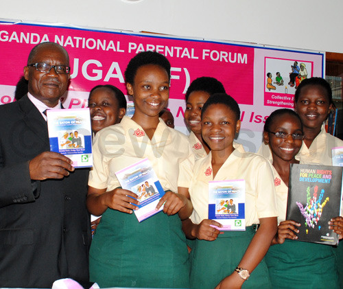 Minister of Gender, Labour and Social Development Mururi Makasa and Students of Gayaza High School launching the Baton of Peace book during the Launch of Uganda National Parental Forum at Gayaza High School. Photo by Mary Kansiime