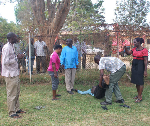 Norman Ahimbisibwe is assisted by onlookers after he collapsed to the Mbarara High Court. Photo by Fred Turyakira