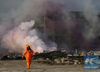 A firefighter works at the explosion site in Tianjin, north China, Aug. 13, 2015.(Xinhua/Shen Bohan)