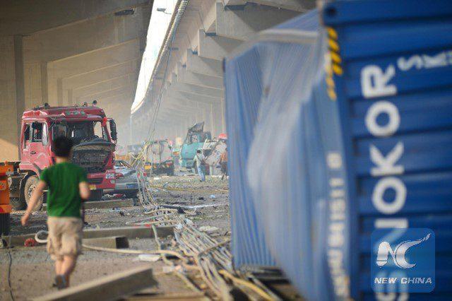 Vehicles are damaged under a bridge near the explosive site in Binhai New Area of Tianjin. (Xinhua)