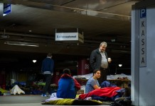 "Refugees rest at the parking lot of a railway station in Salzburg, Austria, on Sept. 14. 2015. German Interior Minister Thomas de Maiziere on Sunday announced that Germany temporarily reinstates border control amid the ongoing refugee crisis. According to German newspaper ""Passauer Neue Presse"", the German government also stopped the trains to and from Austria. (Xinhua/Qian Yi)"