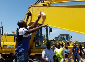 Mr Ibrahim Mahama (left) removing the company's name from one of the state equipment when he returned them to the Multi Purpose Industrial Park in Tema.