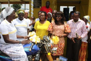 MRS FIAGBENU HANDING OVER THE KEYS TO THE TRICYCLE TO A MEMBER OF SUNG SUMA WOMEN GROUP