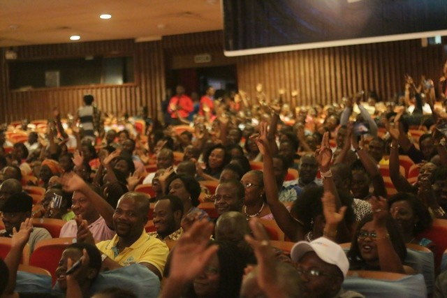 A cross section of audience congratulating cast of the drama