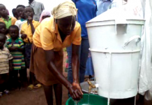 School Pupils watching their colleagues washing their hands with soap and running water.