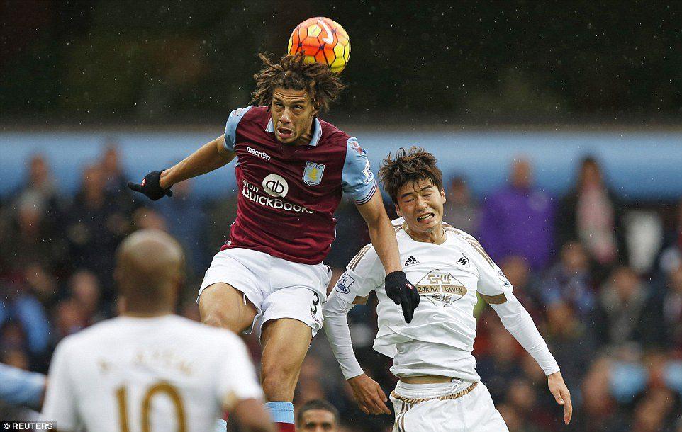 Aston Villa's Rudy Gestede gets his head on the ball to flick it on ahead of Swansea midfielder Ki Sung-Yueng